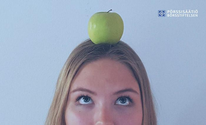 Nainen tasapainottelee päänsä päällä omenaa pohtiva ilme kasvoillaa. Sijoituskoulu: Näin valitset sijoituskohteet