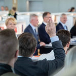 Kuvassa Rinteen hallituksen puolueiden puheenjohtajat pitävät tiedotustilaisuutta hallitusohjelmasta. Etualalla yleisöstä joku viittaa esittääkseen kysymyksen. © Jussi Toivanen/valtioneuvoston kanslia.
