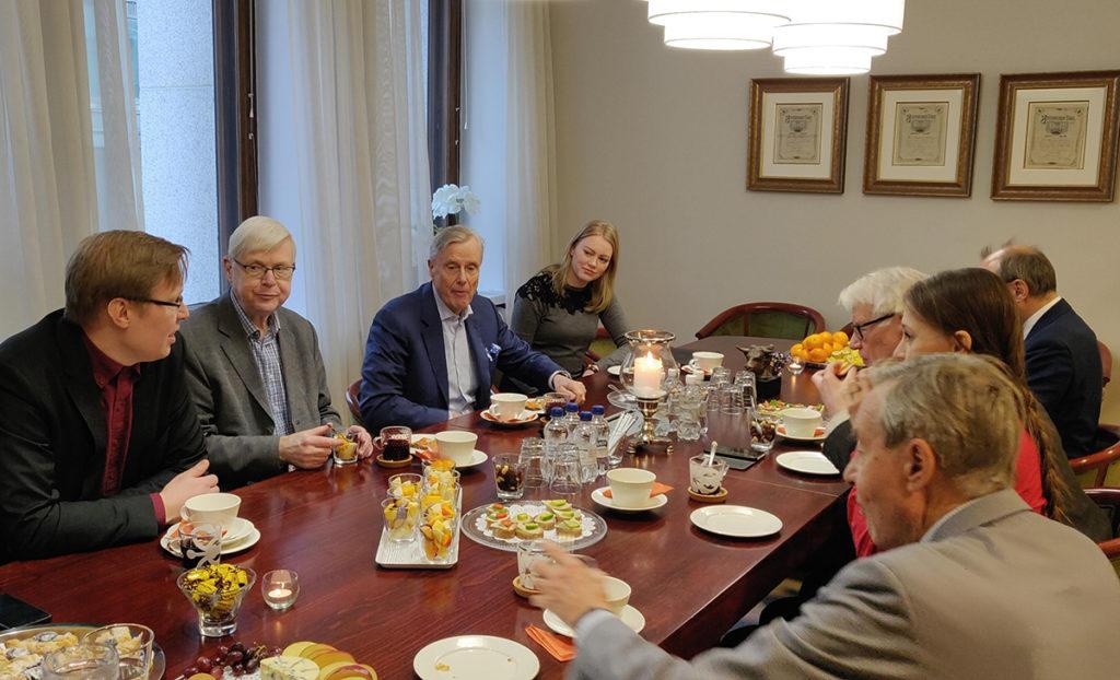 Kokeneita sijoittajia keskustelee pöydän ympärillä sijoittamiseen liittyvistä asioista.